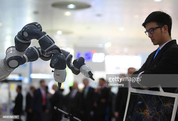 An attendee looks at a YuMi robot manufactured by ABB Ltd at the company's exhibition trade stand at the Hanover industrial fair in Hanover Germany...