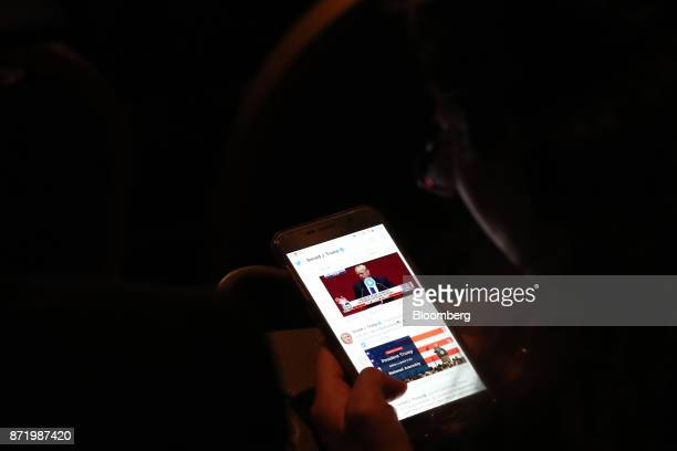 An attendee looks at tweets by US President Donald Trump @realDonaldTrump on a smartphone during the AsiaPacific Economic Cooperation CEO Summit in...