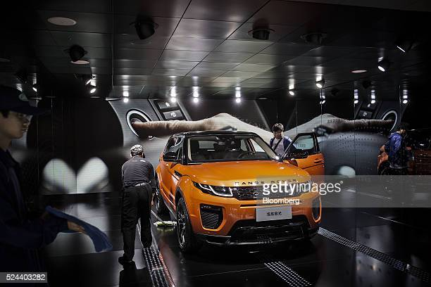 An attendee looks inside a Range Rover Evoque sport utility vehicle produced by Tata Motors Ltd's Jaguar Land Rover unit on display at the Beijing...