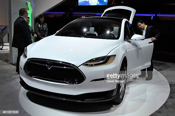An attendee looks over the Telsa Model X all electric vehicle at the Panasonic booth at the 2015 International CES at the Las Vegas Convention Center...
