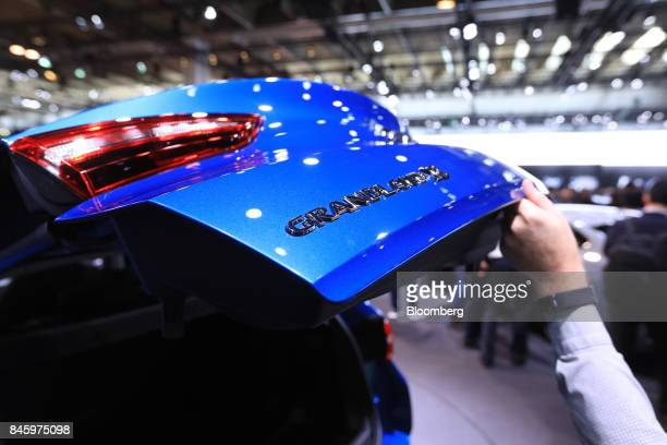 An attendee opens the boot of a Opel AG Grandland X automobile manufactured Adam Opel AG a unit of the PSA Group during the first media preview day...