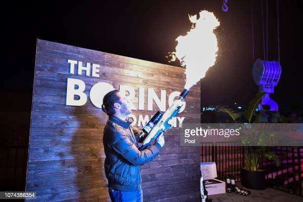 An attendee operates a Boring Co. Flamethrower at the company's photo booth during an unveiling event for The Boring Company Hawthorne test tunnel...