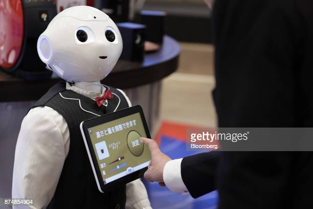 An attendee orders a cup of coffee via the touch screen on a SoftBank Group Corp Pepper humanoid robot during a media preview of the humanless cafe...