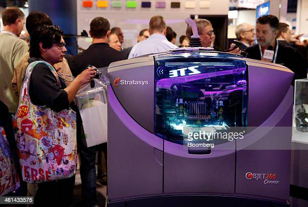 An attendee photographs a Stratasys Ltd 3D printer during the 2014 Consumer Electronics Show in Las Vegas Nevada US on Wednesday Jan 8 2014 The CES...