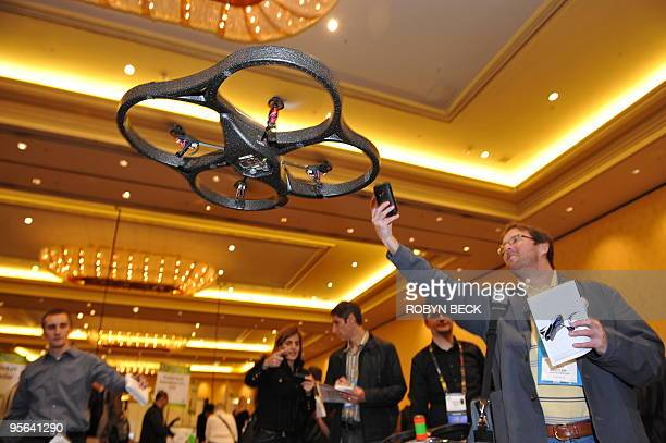 An attendee photographs an A.R. Drone helicopter by Parrot as it flies overhead during a press event for the 2010 International Consumer Electronics...