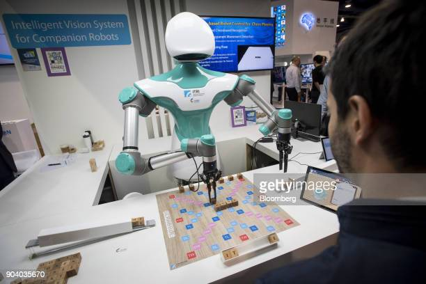 An attendee plays a game of Scrabble against an Industrial Technology Research Institute Intelligent Vision System companion robot during the 2018...