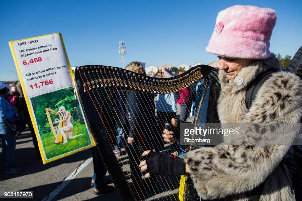 An attendee plays a harp outside before entering the Sam Boyd Stadium during the Womens March OneYear Anniversary Power To The Polls event in Las...