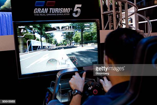 An attendee plays Gran Turismo on Sony Corp's Playstation 3 during the 2010 International Consumer Electronics Show in Las Vegas Nevada US on...