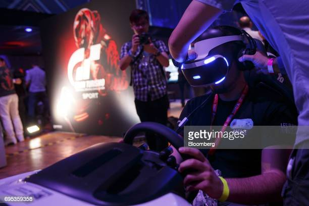 An attendee plays Gran Turismo Sport in a Sony Corp PlayStation 4 gaming car seat with a VR headset before a Sony event ahead of the E3 Electronic...