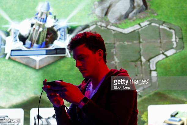 An attendee plays the Command and Conquer Rivals video game on a mobile device during an Electronic Arts Inc event ahead of the E3 Electronic...