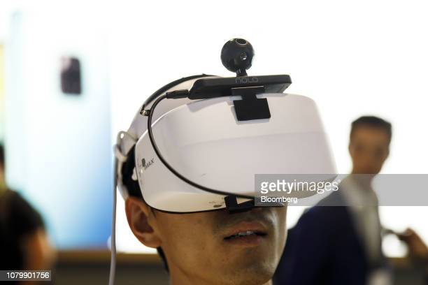 An attendee plays the Huawei VR2 virtual reality music game with NOLO VR tracking at the Huawei Technologies Co booth at the 2019 Consumer...