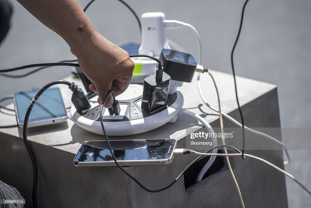 An attendee plugs in a charging cord during the Google I/O Annual Developers Conference in Mountain View, California, U.S., on Wednesday, May 18, 2016. Google unveiled a new video calling application named Duo that will compete with Apple Inc.'s FaceTime. Photographer: David Paul Morris/Bloomberg via Getty Images