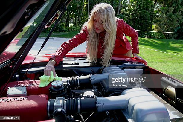 An attendee polishes the engine of her 2004 Ferrari SpA 360 sports vehicle during the 26th Annual Cavallino Classic Event at the Breakers Hotel in...