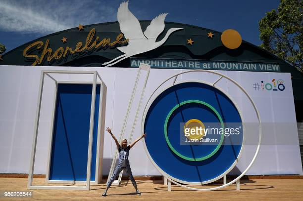 An attendee poses for a photo in front of the Google I/O logo at the Google I/O 2018 Conference at Shoreline Amphitheater on May 8 2018 in Mountain...