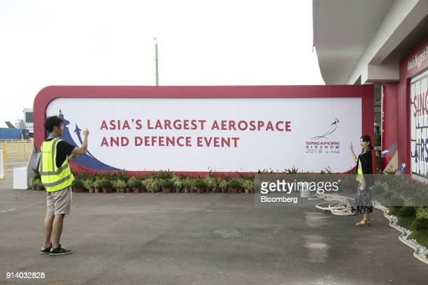 An attendee poses for a photograph in front of a sign during a media preview day at the Singapore Airshow held at the Changi Exhibition Centre in...