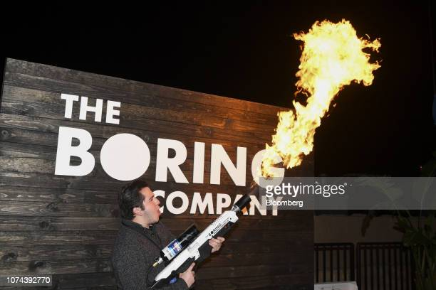 An attendee poses for a photograph while operating a Boring Co. Flamethrower at an unveiling event for the company's Hawthorne test tunnel in...