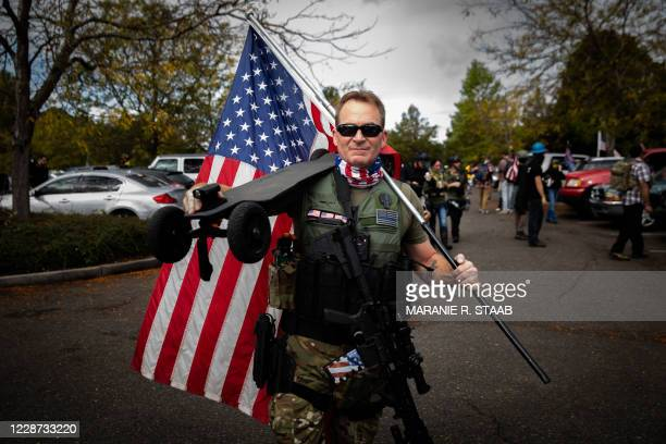 An attendee poses for a picture before listening to organizers speak during a Proud Boys rally at Delta Park in Portland, Oregon on September 26,...