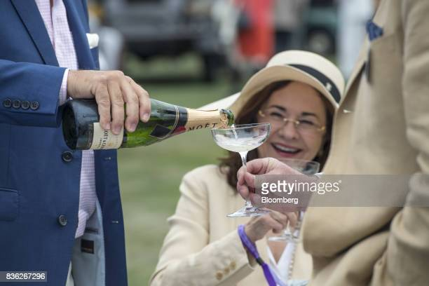 An attendee pours Moet Chandon champagne into a glass during the 2017 Pebble Beach Concours d'Elegance in Pebble Beach California US on Sunday Aug 20...