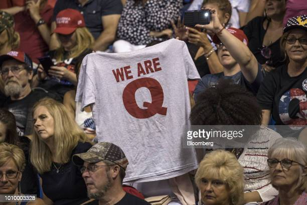 An attendee raises up a Tshirt with the words We Are Q before the start of a rally with US President Donald Trump in WilkesBarre Pennsylvania US on...