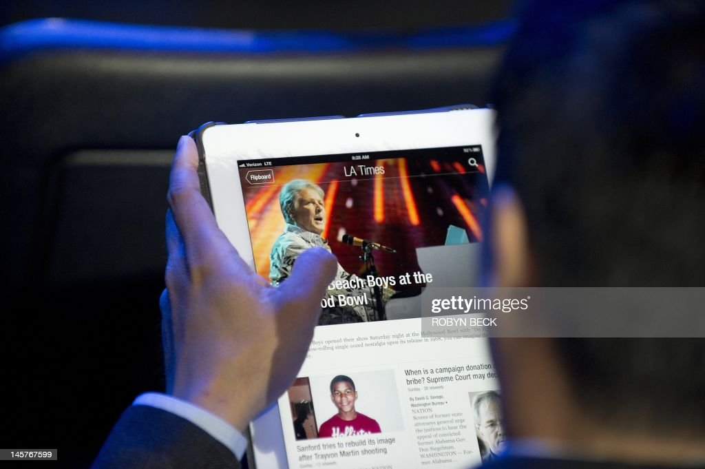 An attendee reads a Los Angeles Times ne : News Photo