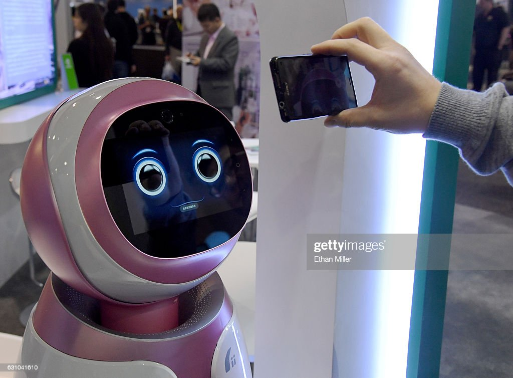 An attendee records images of a prototype Kikoo autonomous robot for children made by Hanwuji Intelligence at CES 2017 at the Sands Expo and Convention Center on January 5, 2017 in Las Vegas, Nevada. The USD 600 robot features facial recognition technology and is designed to be a companion to children when their parents are working. Using age-based interactive content, it can launch talks or songs actively and dance or play with children as well as automatically take photos and video using voice or app instruction. CES, the world's largest annual consumer technology trade show, runs through January 8 and features 3,800 exhibitors showing off their latest products and services to more than 165,000 attendees.