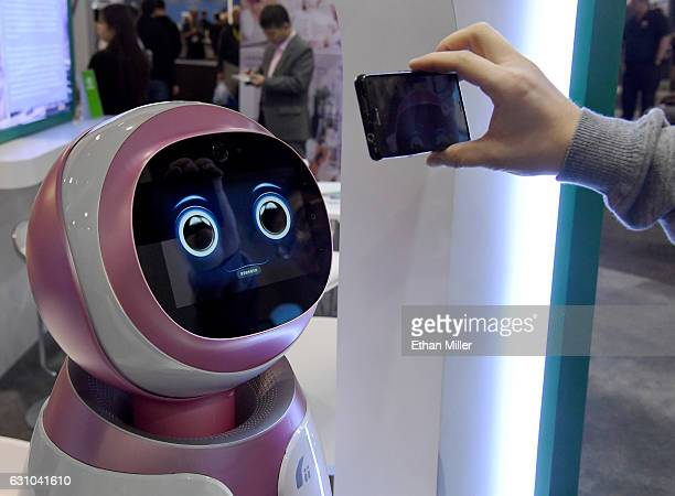 An attendee records images of a prototype Kikoo autonomous robot for children made by Hanwuji Intelligence at CES 2017 at the Sands Expo and...