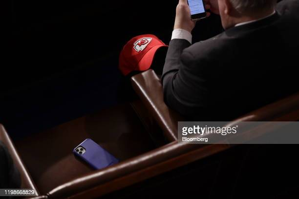 An attendee rests a hat displaying the logo of the Kansas City Chiefs National Football League on his knee ahead of a State of the Union address to a...
