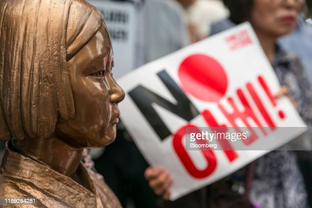 An attendee, right, holds a placard reading 'No Abe!' next to the statue of a girl representing a 'comfort woman' in world war two during a...
