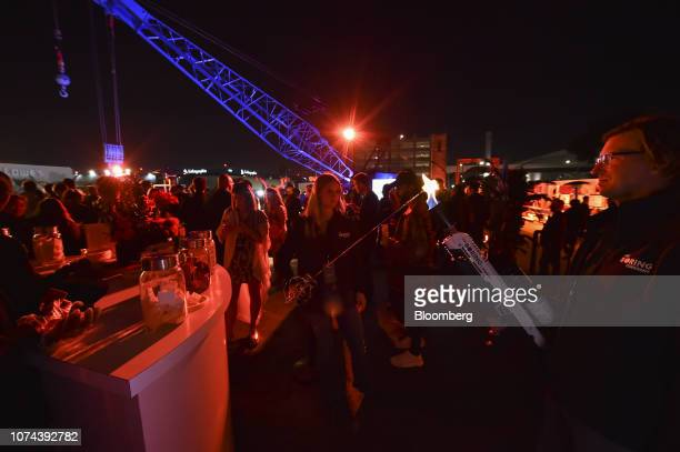 An attendee, right, operates a Boring Co. Flamethrower to toast a marshmallow at an unveiling event for the company's Hawthorne test tunnel in...