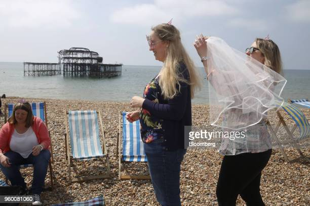 An attendee right prepares to place a veil on the head of another attendee during a royal wedding viewing party overlooking the sea in Brighton...