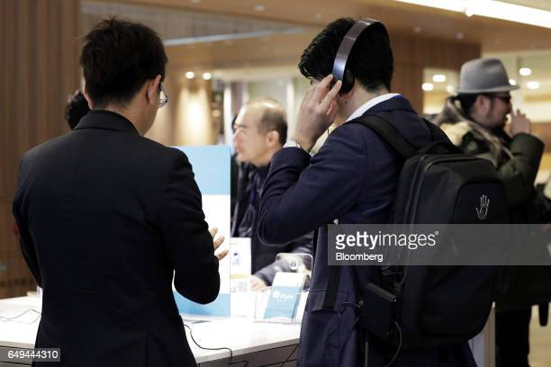 An attendee right tries out a SubPac Inc B1 backpac accessory for the S2 seatback tactile bass system at a SoftBank Corp Style media event in Tokyo...