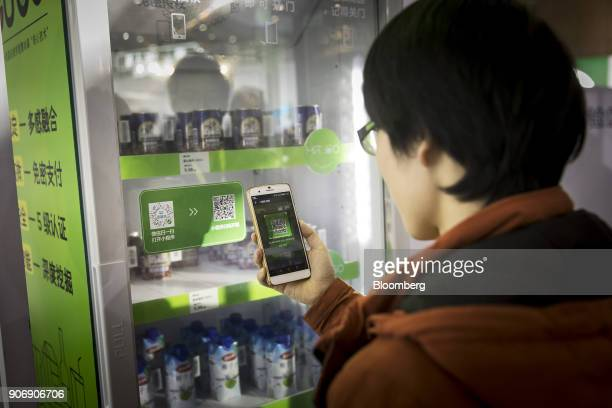 An attendee scans a QR code with his smartphone to purchase a drink from a vending machine at Tencent Holdings Ltd's WeChat Open Class Pro conference...