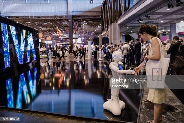 An attendee shakes hands with a 'Pepper' humanoid robot manufactured by SoftBank Group Corp at the Viva Technology conference in Paris France on...