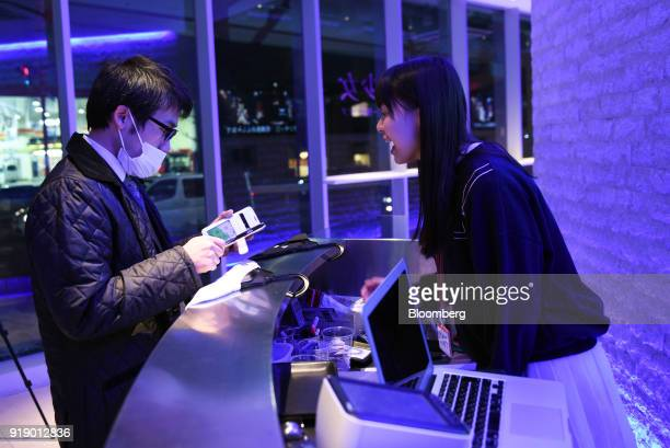 An attendee shows his mobile phone at the entrance ahead of a concert by Japanese pop group 'Virtual Currency Girls' in Tokyo Japan on Friday Feb 16...
