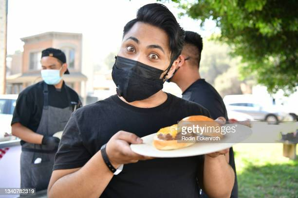 """An attendee shows off a burger during """"Toretto Family BBQ"""" at the F9 Fest event on the Universal Studios backlot celebrating F9: The Fast Saga on..."""
