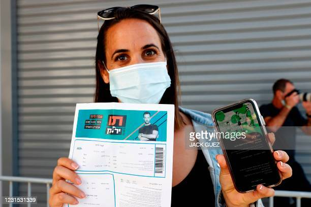 """An attendee shows off a """"green pass"""" upon arrival at Bloomfield Stadium in the Israeli Mediterranean coastal city of Tel Aviv on March 5 before..."""