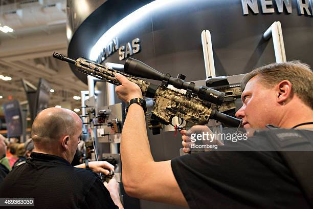 An attendee sights a rifle in the Sig Sauer Inc booth on the exhibition floor of the 144th National Rifle Association Annual Meetings and Exhibits at...