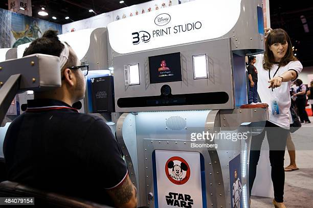 An attendee sits for a face scan at the Walt Disney Co's 3D Print Studio booth during the D23 Expo 2015 in Anaheim California US on Friday Aug 14...