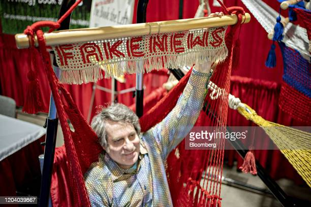 An attendee sits in a Fake News hammock in the exhibition hall during the Conservative Political Action Conference in National Harbor Maryland US on...