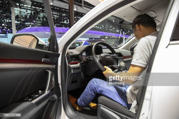 An attendee sits inside a Great Wall Motor Co Haval H4 sport utility vehicle at the Guangzhou International Automobile Exhibition in Guangzhou China...