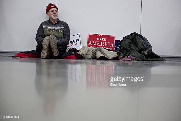 An attendee sits next to placards as he waits for U.S. President-elect Donald Trump, not pictured, to arrive during an event in West Allis,...