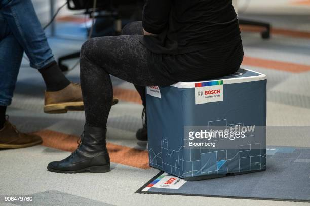 An attendee sits on a Bosch #streetflow ebike branded stool as Robert Bosch GmbH opens an Internet of Things campus in Berlin Germany on Thursday Jan...