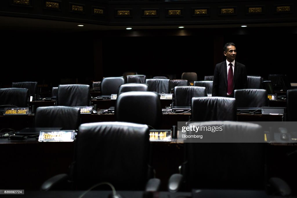 An attendee stands among empty pro-government deputies' chairs during a special session of the National Assembly of Caracas, Venezuela, on Saturday, Aug. 19, 2017. Venezuela's new legislative super body took over the functions of the country's only remaining opposition-run institution -- the National Assembly -- by approving a decree that empowers it to pass laws on a range of issues. Photographer: Wil Riera/Bloomberg via Getty Images
