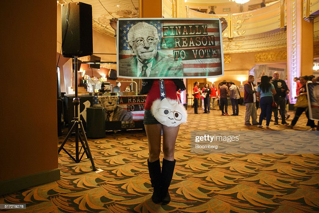 An attendee stands for a photograph while holding a poster during a campaign event for Senator Bernie Sanders, an independent from Vermont and 2016 Democratic presidential candidate, not pictured, at The Wiltern in Los Angeles, California, U.S., on Wednesday, March 23, 2016. Sanders won the Democratic caucuses in Utah, according to the Associated Press, while votes were still being counted in the state's Republican caucuses and the Democratic caucuses in Idaho. Photographer: Patrick T. Fallon/Bloomberg via Getty Images