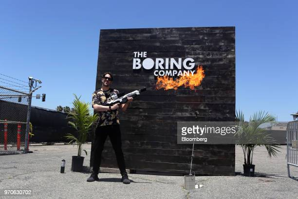 An attendee stands for a photograph while operating a Boring Co. Flamethrower during the company's Not-a-Flamethrower Party outside of the Space...