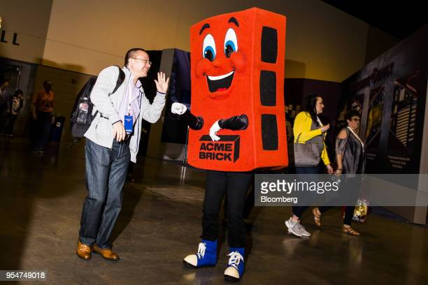 An attendee stands for a photograph with the Acme Brick Co mascot during a shareholders shopping day ahead of the Berkshire Hathaway annual meeting...