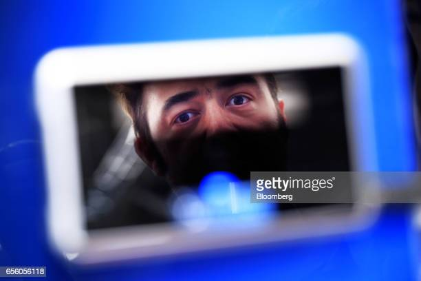 An attendee stands in front of an iris scanning camera to test the operation of an iris recognition system at the Dermalog Identification Systems...