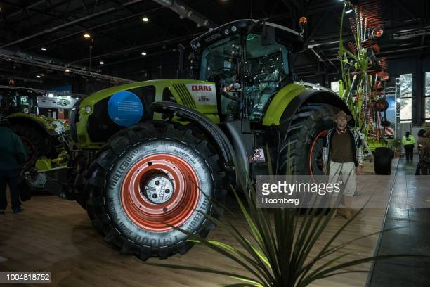 An attendee stands next to Claas KGaA Axion tractor at the exhibition pavilion during La Exposicion Rural agricultural and livestock show in the...