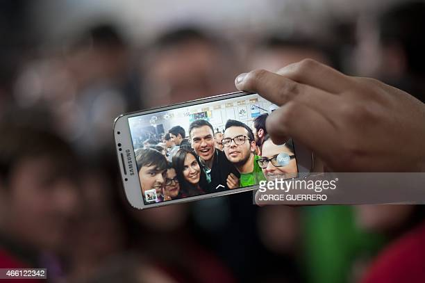 An attendee takes a photo with a mobile phone of Secretary General of the Spanish Socialist Workers' Party Pedro Sanchez posing with young supporters...