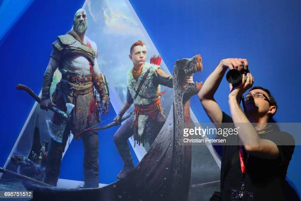 An attendee takes a photograph near an ad for 'God of War 4' during the Electronic Entertainment Expo E3 at the Los Angeles Convention Center on June...